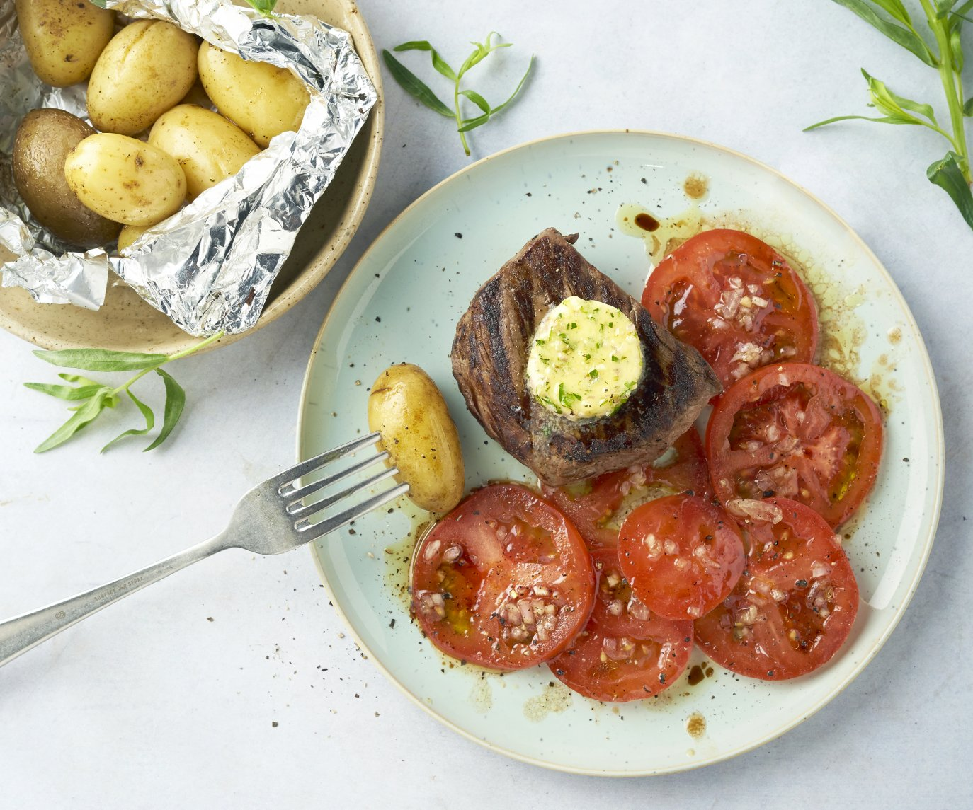 Steak met dragon-lookboter, tomatensalade en krieltjes